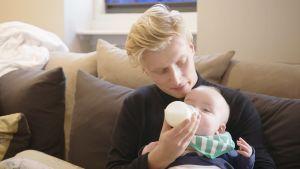 Iigi juottaa sohvalla vauvalle maitoa tuttipullosta.
