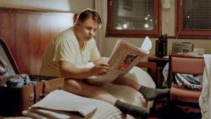 Mies istuu sängyllä ja lukee sanomalehteä.