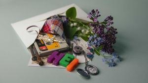 Avonainen kirjekuori, jonka sisällä on kaikkea pientä kivaa: koruja, c-kasetti, kukkia, muovisia kirjaimia jne.