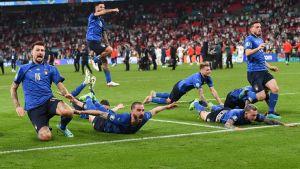 Sinisiin pukeutuneet jalkapallon pelaajat pelitilanteessa kentällä.