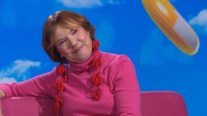 Kirjailija Rosa Liksom Puoli seitsemän -ohjelman studiossa ja istuu sohvalla.