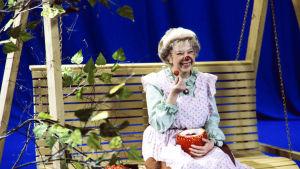 Äitiliini (Raili Veivo) syö mansikoita keinussa.