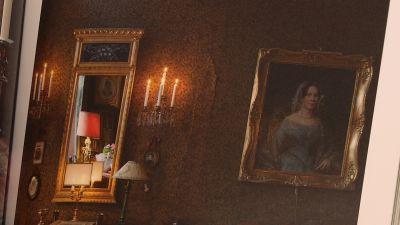 En tapetserad vägg med empirspegel och portträtt av dam