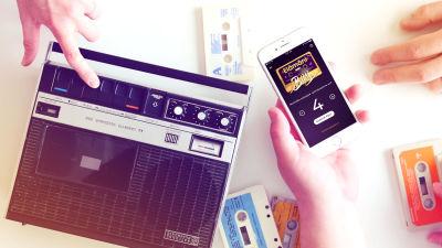 kuva käsistä jotka pitää kännykkää, pitää kasettia ja painaa play kasettiradiosoittimessa.