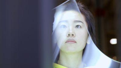 Närbild på en glasarbetare på Fuyao-fabriken, personen håller i ett stort glasfönster till en bil.