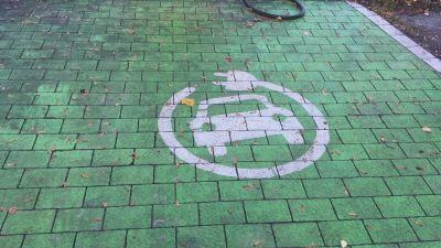 Grön färg på asfalt som visar var man kan ladda elbilar.