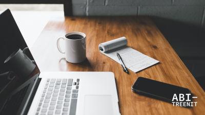 Työpöytä, jossa tietokone, muistilehtiö ja kahvikuppi.