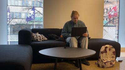 En ung man sitter i en soffa och ser på en bärbar dator och har en väska bredvid sig.