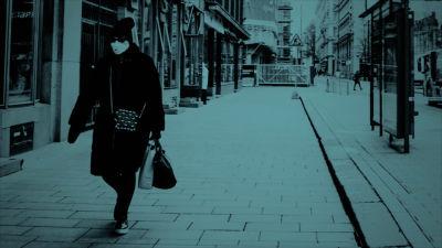 Kvinna med munskydd på Alexandersgatan i Helsingfors med rött filter.