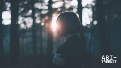 nainen metsässä auringonlaskussa