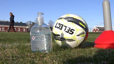 En handdesinficeringsflaska och en fotboll står på en gräsplan.