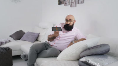Ali Jahangiri istuu siistissä kodissa, keskustelee kännykän kanssa.