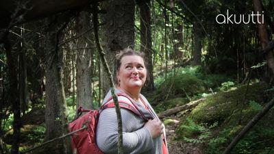 psykologi Liisa Uusitalo-Arola metsäretkellä reppu selässä iloisen näköisenä