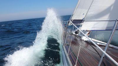 Vågorna slår i sidan på segelbåten.