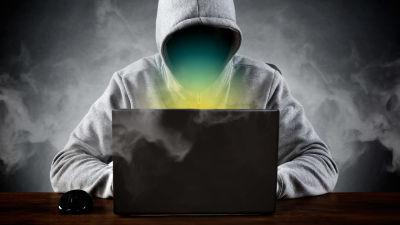 Tunnistamaton huppupäinen harmo käyttää tietokonetta. Koneen näyttä hehkuu ja ympärillä on savua.