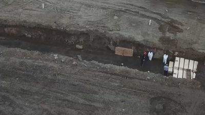 Tiotals kistor begravs av vitklädda arbetare på Hart Island utanför New York.