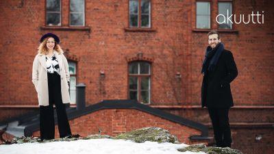 Positiivisen pedagogiikan tutkija Kaisa Vuorinen ja psykologi Jaakko Sahimaa seisovat vanhan punatiilisen rakennuksen edustalla ja hymyilevät kameralle.
