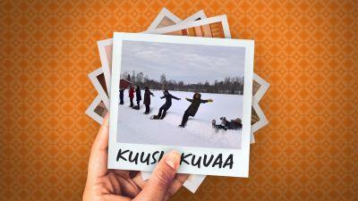 Noin kymmenen henkilöä seisoo lumisessa maisemassa tien reunassa, ja he oat kaatumassa taaksepäin selilleen pehmeään lumihankeen