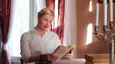 Anna Tulusto lukee Leo Tolstoin Anna Kareninaa aurinkoisen pöydän äärellä, edessä monihaarainen kynttelikkö