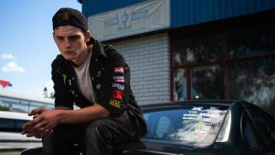 Poika istuu auton takaluukun päällä ja katsoo alaspäin.
