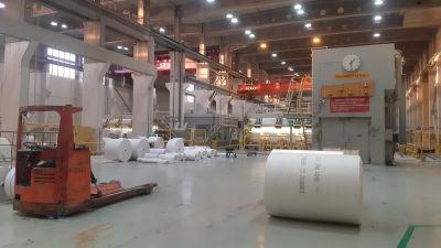 Stora pappersrullar på ett fabriksgolv.
