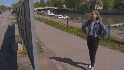 Desirée Kavander, en ung dam med jeansjacka och ljust hår, står med armarna i sidorna och tittar på en ställning för valaffischer.
