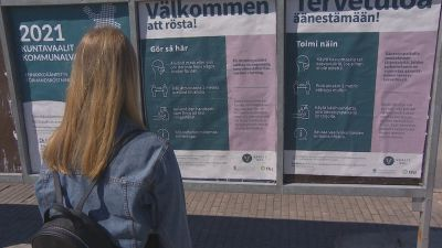 En ung dam med långt ljust hår och en jeansjacka ser på uteaffischer om hur kommunalvalet 2021 går till.
