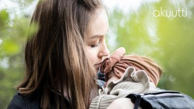 Jonna Poutala pitää lähikuvassa kolmen kuukauden ikäistä Adessa-vauvaa sylissään. Taustalla vehreitä puita.