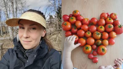 Ponihäntäinen nainen ruskeassa puutarhassa katsoo kameraan, toisella puolella pöydällä tomaatteja