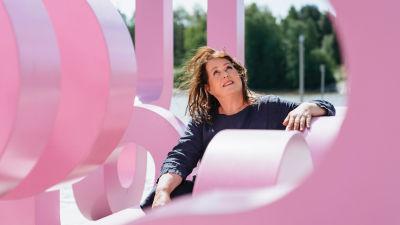 Nainen istuu abstraktin vaaleanpunaisen patsaan keskellä, katsoo ylöspäin.