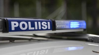 Närbild på polisskylt med blåljusen på i en polisbil.