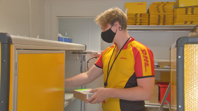 Ett cykelbud i gul skjorta sätter in frakt i sin cykels gula låda.