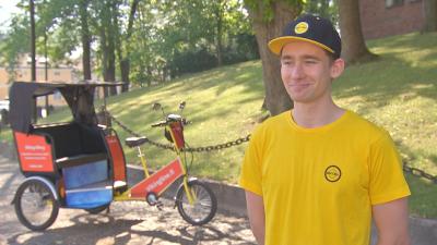 En man med gul skjorta och keps står vid sin cykeltaxi, riksha, vid en park en varm sommardag.