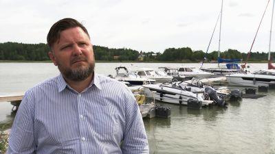 En man i blårandig skjorta står framför en brygga med båtar.