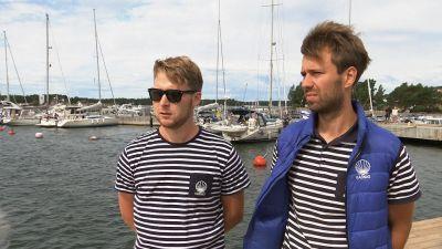 Två unga män står framför en brygga med båtar.