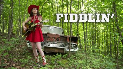 Nuori nainen cowboybootseissa ja -hatussa kitara kädessä mets'ss, kuvan päällä otsikko Fiddlin'.