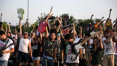 Iso joukko iloisia ihmisiä kitarat kädessä. Kuva dokumenttielokuvasta We Are The Thousand.