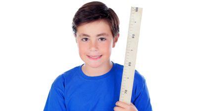Leende ung pojke mes stor linjal i handen