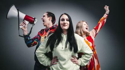Atte Ahokas huutaa megafoniin, Ellen Ojala katsoo suoraan kameraan ja Elina Arpala pitää kättä ylhäällä