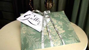 En present som är inslagen i tapetrester med ett handskrivet gratulationskort.