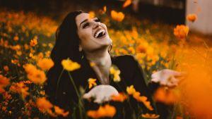 Nainen iloitsee kukkaniityllä.
