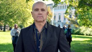 John Hassler i mörk kostym i en lummig park på Stockholms universitetsområde.
