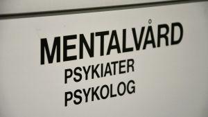 En vit skylt med svart text: Mentalvård, psykiater, psykolog