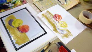 En glasskiva där man målat två äppel och ett pappersark där målningen är avtryckt, en så kallad monprint..