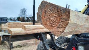 stock som sticker ut på släpet av en skogsmaskin.