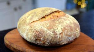 Ett nygräddat bröd på en skärbräda.
