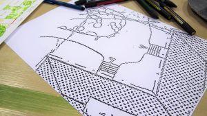 En del av en situationsplan på ett bord tillsammans med en trädgårdsplan och några tuschpennor.