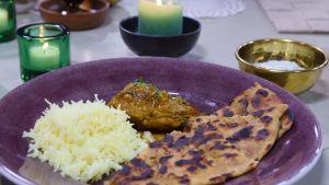 En portion med kyckling, ris och bröd på ett fat