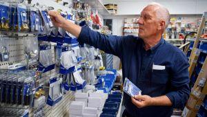 Stig Eggert placerar hänglås på vägghyllan i en butik.
