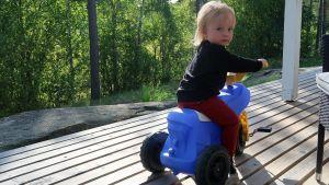 Ett litet barn på en blå tramptraktor, på en terass, skogen i bakgrunden.